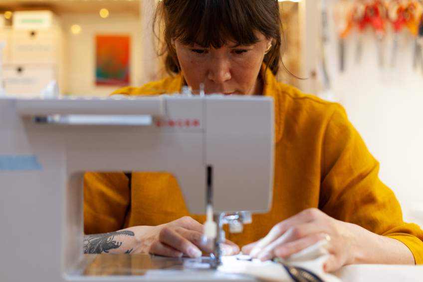 Photo of Ellie Lum of Klum House sewing