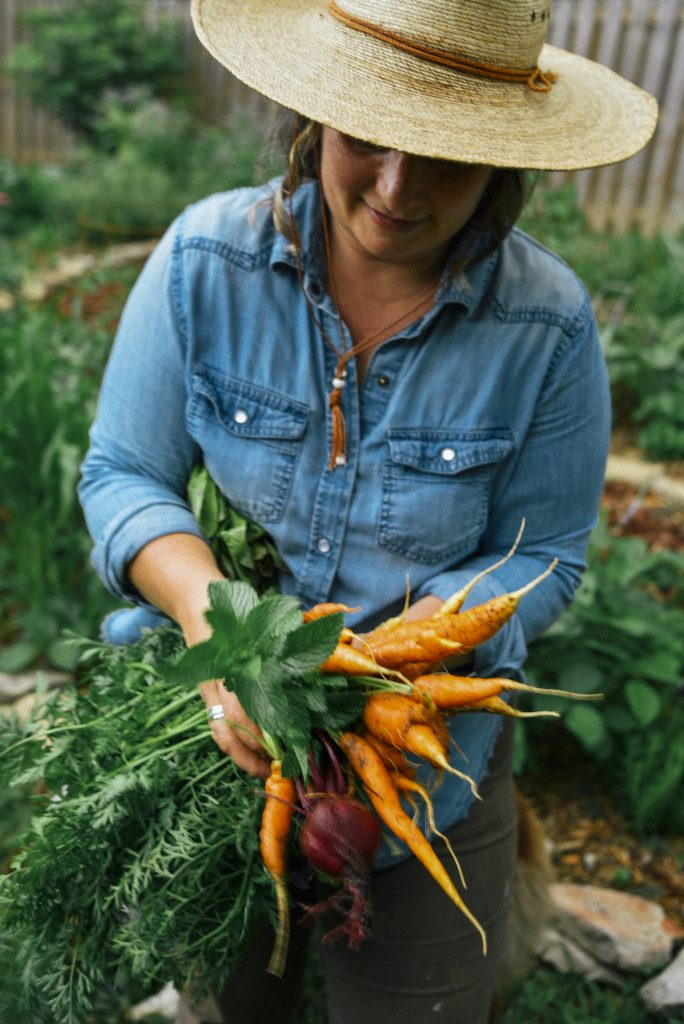 Kelly Smith Trimble with carrots in her garden.